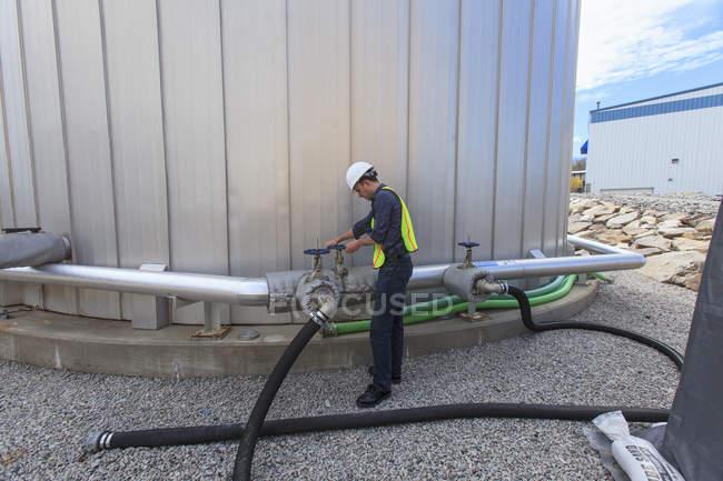 Ingénieur industriel tournant la vanne sur le tuyau au réservoir de carburant d'une centrale électrique — Photo de stock