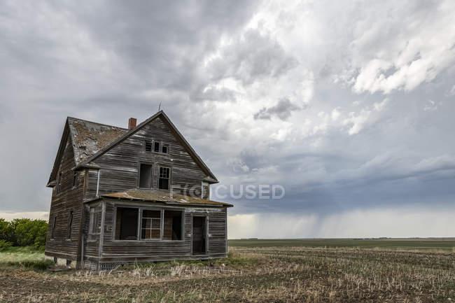 Vecchia fattoria sulle praterie sotto le nuvole di tempesta; Val Marie, Alberta, Canada — Foto stock