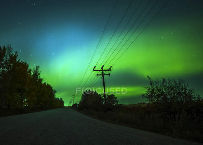 Northern Lights glowing green in the starry sky above a rural road and transmission lines, Sturgeon County; Alberta, Canada — Stock Photo