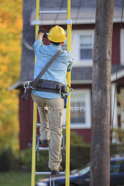 Lineman climbing ladder at power pole — Stock Photo