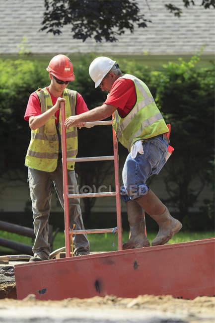 Будівельники спускаються драбиною. — стокове фото
