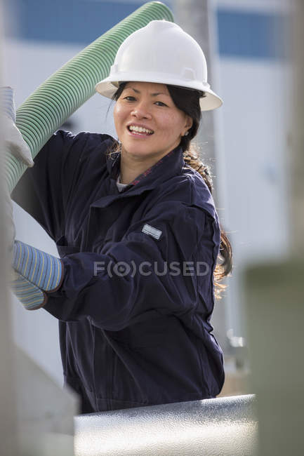 Ingénieur électrique femelle déplaçant un tuyau flexible à la centrale — Photo de stock