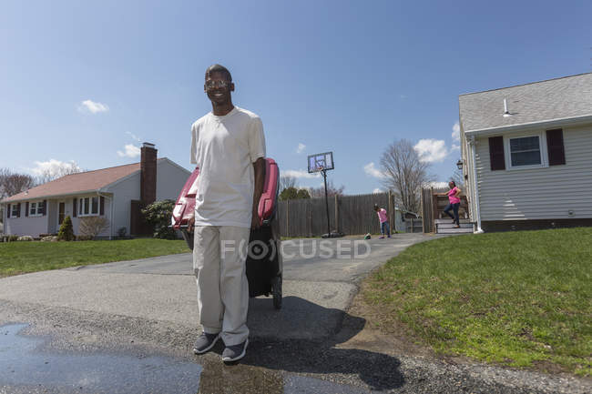 Man with Williams Syndrome taking out the trash with family in the background — Stock Photo