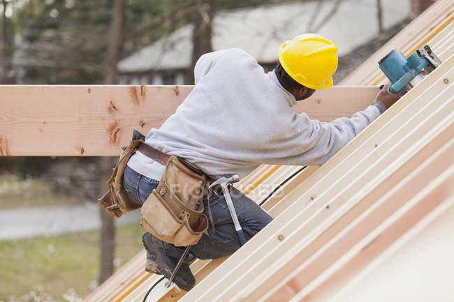Плотник с помощью циркулярной пилы на балке — стоковое фото