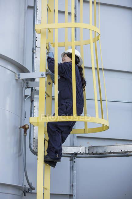 Engenheira de energia feminina escalando dentro da escada da gaiola de segurança na central elétrica — Fotografia de Stock