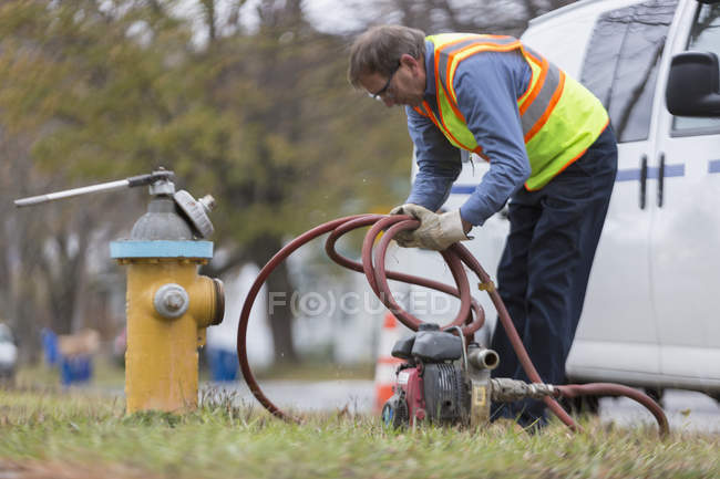 Water department technician coiling hose used to flush hydrant — стокове фото