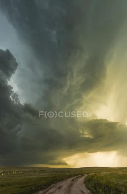 Supercell sobre las praderas y un camino de tierra, con la luz del sol iluminando el cielo dramático; Tulsa, Oklahoma, Estados Unidos de América - foto de stock