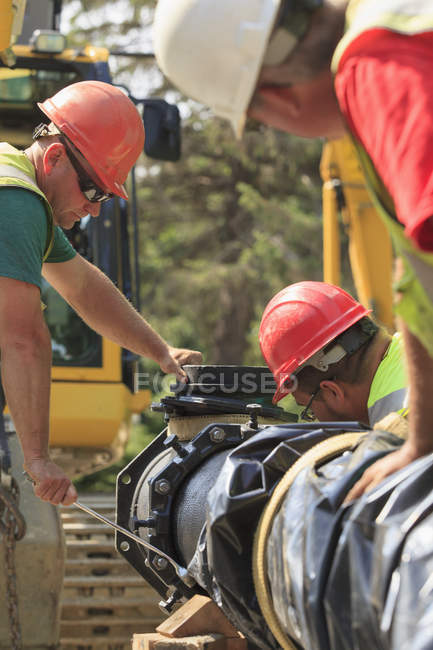 Construction workers using hand wrench to secure water main section with bolts — Stock Photo