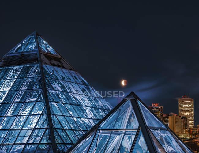 Un eclipse lunar sobre el centro de Edmonton y el Conservatorio de Muttart; Edmonton, Alberta, Canadá - foto de stock