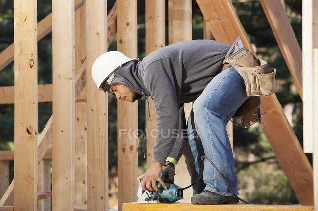 Faisceau de coupe de charpentier à longueur à l'aide d'une scie circulaire — Photo de stock