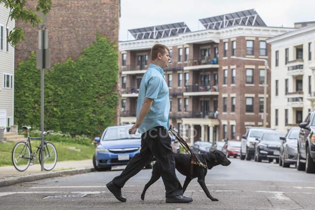 Hombre con discapacidad visual paseando con su perro de servicio - foto de stock