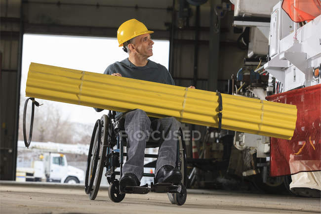 Maintenance supervisor with spinal cord injury preparing to load shielding onto utility truck — Stock Photo