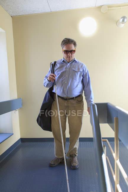 Мужчина с врожденной слепотой с помощью трости в коридоре квартиры — стоковое фото