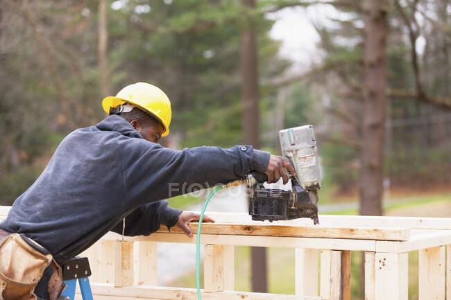 Карпентер за допомогою цвяхового пістолета обрізає будинок. — стокове фото