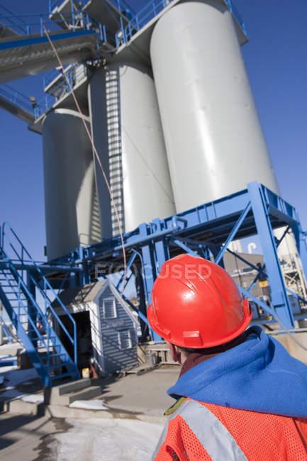 Инженер, осматривающий транспортер в силосы для материалов на промышленном предприятии — стоковое фото