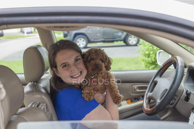 Young Woman with Cerebral Palsy holding her dog in the car — Stock Photo