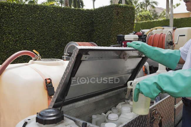 Tecnico di controllo dei parassiti presso il contenitore di stoccaggio chimico su camion — Foto stock