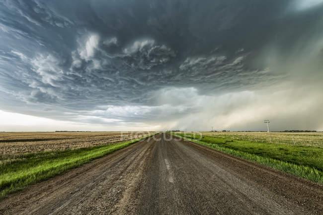 Гравійна дорога веде на відстань до драматичних штормових хмар; Валь - Марі (Саскачеван, Канада). — стокове фото