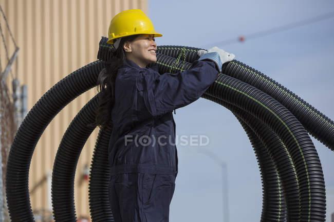 Ingeniera de potencia femenina moviendo tubos de drenaje flexibles - foto de stock