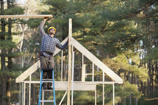 Charpentier assemblant la structure du toit pour la construction de la maison — Photo de stock