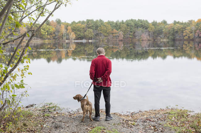 Man with Anxiety Disorder and his therapy dog at a lake — Photo de stock
