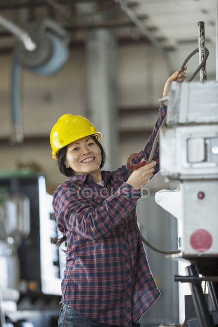 Female power engineer securing cable to equipment truck — Stock Photo