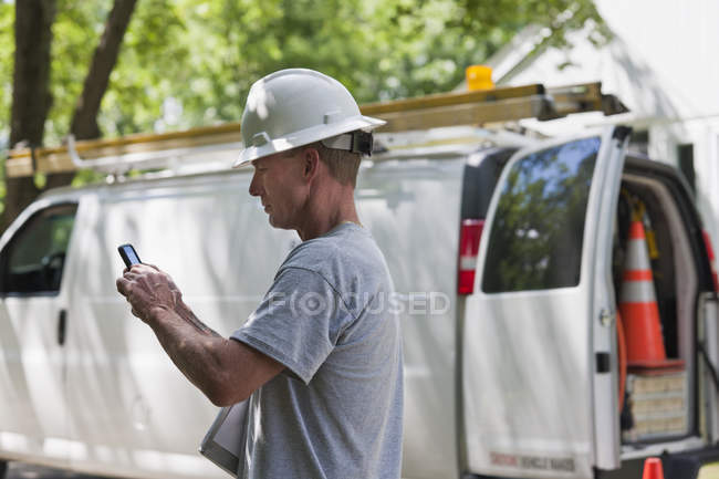 Cable installer reviewing work order for installation on smartphone — стокове фото