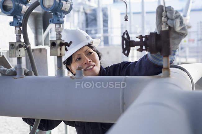 Жіночий інженер перевіряє датчики тиску на електростанції. — стокове фото