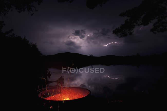 Ночью в озере Умбагог, штат Нью-Гемпшир, США, вспыхнул пожар с молнией на заднем плане — стоковое фото
