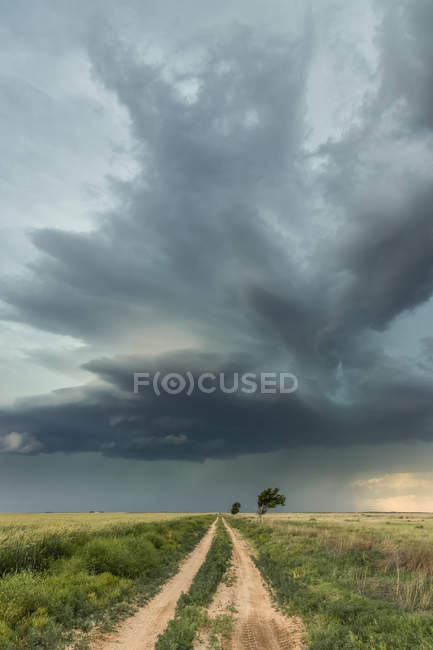 Супермобільник над преріями і ґрунтова дорога, з сонячним світлом, що освітлює драматичне небо; Талса, Оклахома, Сполучені Штати Америки — стокове фото