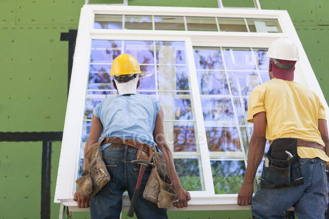 Carpenters positioning a large window frame at a construction site — Stock Photo