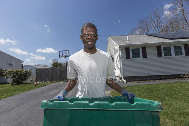 Man with Williams Syndrome taking out the trash — Stock Photo