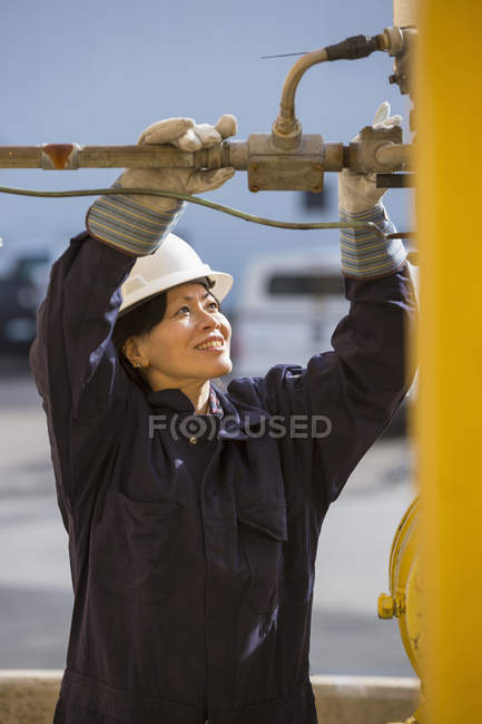 Female power engineer checking fuel line sensors at power plant — Stock Photo