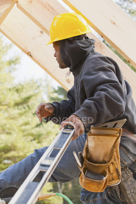 Carpenter using a level in house construction — Stock Photo