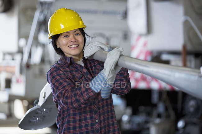 Жіночий інженер пересуває вуличну лампу в службовому гаражі. — стокове фото