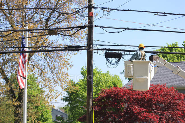 Power engineer riding in lift bucket to work on power lines — Stockfoto