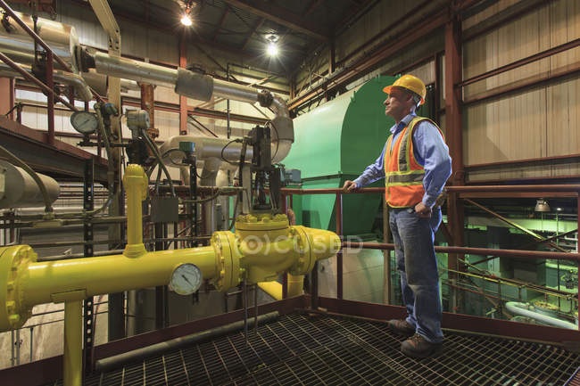 Engineer in electric power plant inspecting condenser room piping — Stock Photo