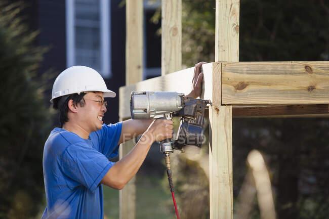 Carpinteiro usando pistola de ar para instalar moldura deck — Fotografia de Stock