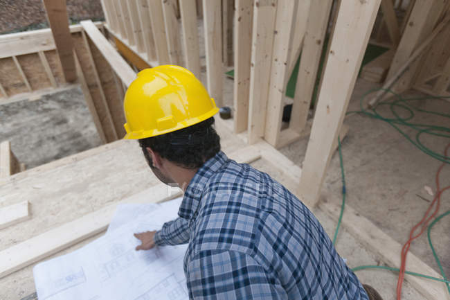 Carpenter reviewing house plans, rear view — Stock Photo