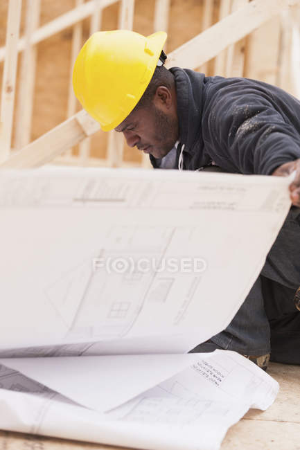 Carpenter reviewing home construction plans on site — Stock Photo
