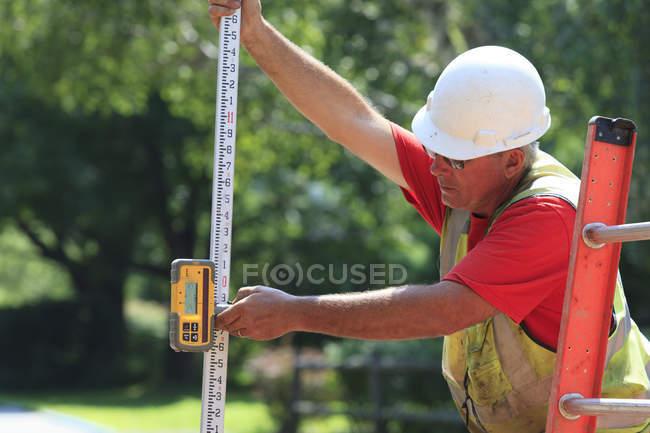 Construction supervisor using electronic surveying rod — Stock Photo