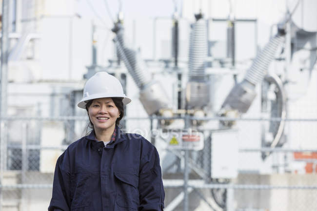 Portrait of female power engineer in front of high voltage transformer at power station — Stock Photo