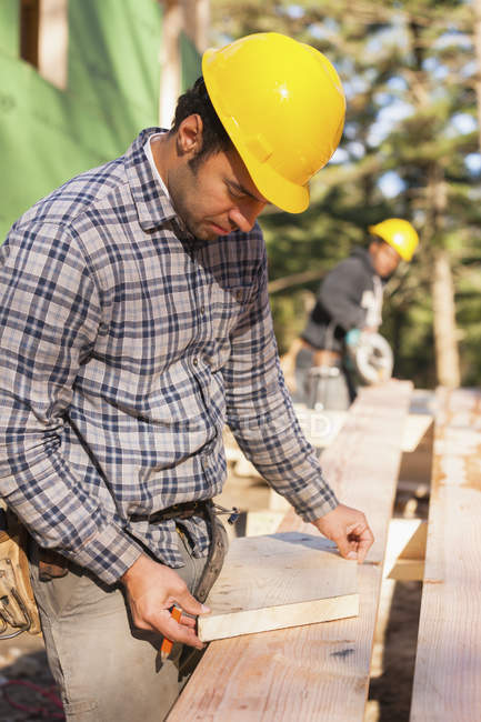 Carpenter preparing bevel cut for a rafter of a house — Stock Photo