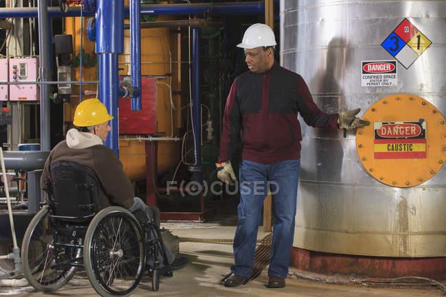 Інженери електростанцій один з травмами спинного мозку обговорюють обладнання демінералізації — стокове фото