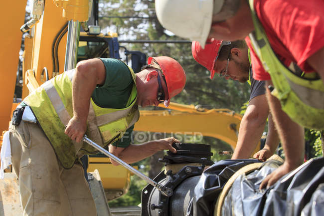 Trabalhadores da construção civil usando chave de torque para fixar a seção principal da água com parafusos — Fotografia de Stock