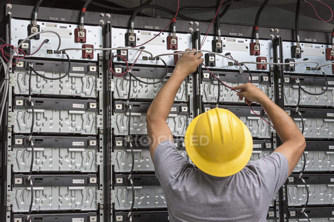 Engineer connecting energy storage batteries for back up power to an electric power plant — Stock Photo