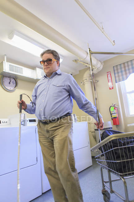 Man with congenital blindness putting his laundry into the laundry cart in the laundry room — Stockfoto