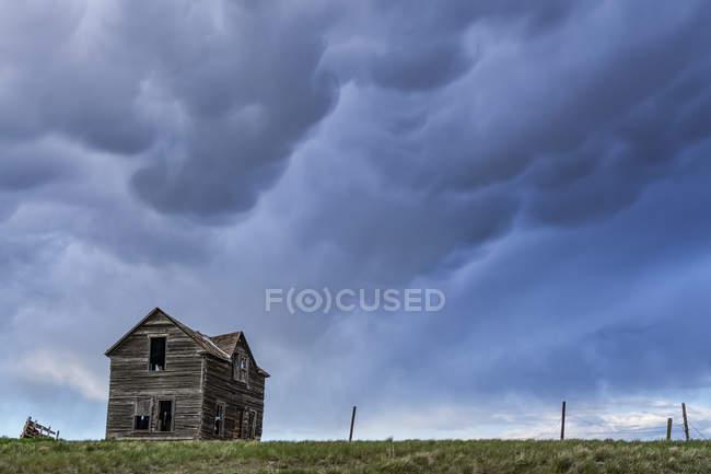 Старая усадьба на прериях под бурным небом; Саскачеван, Канада — стоковое фото