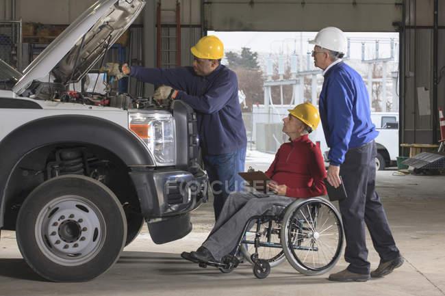 Ingenieros de centrales eléctricas uno con lesión medular revisando el mantenimiento de camiones utilitarios - foto de stock