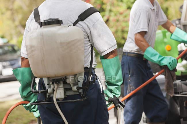Tecnici di controllo parassiti con tubo avvolgitore portatile a spruzzo al camion di servizio — Foto stock